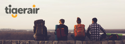 Group of travelling friends sitting on brick wall overlooking a city